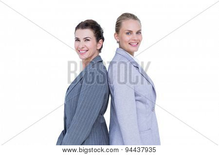 Attractive businesswomen standing back-to-back against white wall