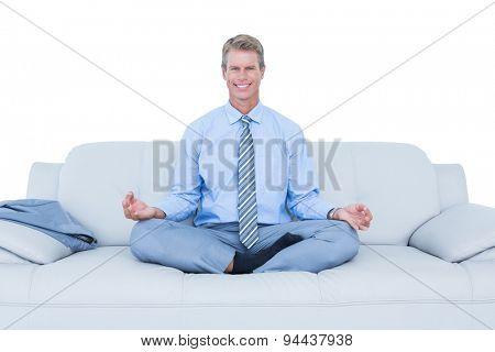 businessman meditating in yoga pose on white background