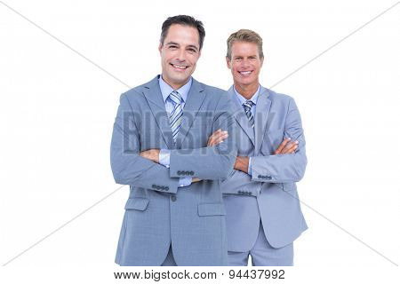 Business team standing arms crossed against a white screen