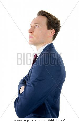 Thoughtful businessman looking away with arms crossed on white background