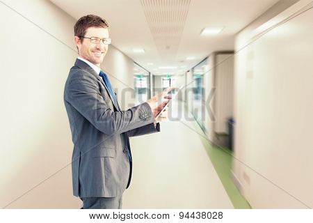 Businessman using his tablet pc against college hallway