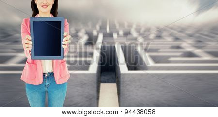 Elegant brunette using tablet against big 3d maze under clouds