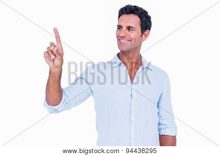 Handsome man pointing something with his finger on white background