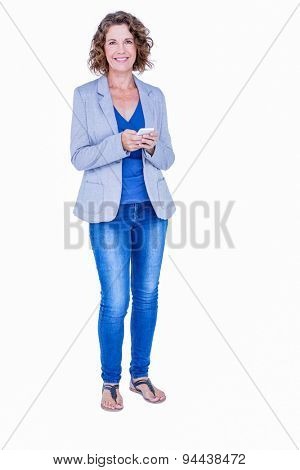 Businesswoman looking at camera and using her smartphone on white background