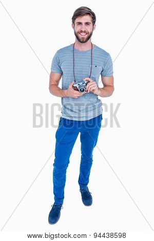 Happy handsome man looking at camera and holding photo camera on white background