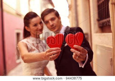Bride And Groom Holding Red Hearts