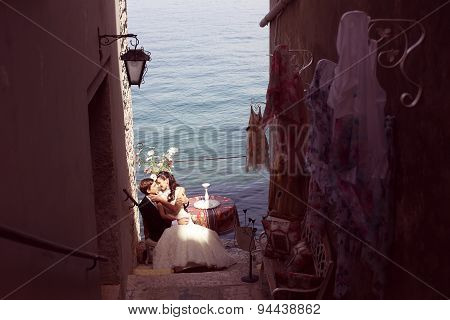 Bride And Groom Kissing Near Ocean