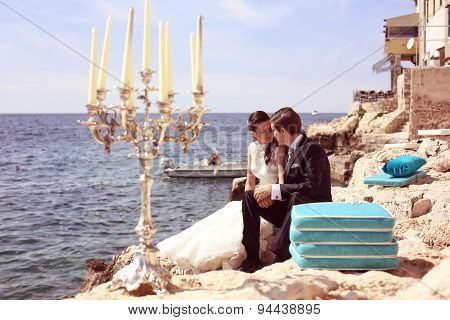 Candles on the beach with bride and groom in background
