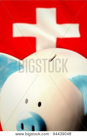 Piggy bank against digitally generated swiss national flag