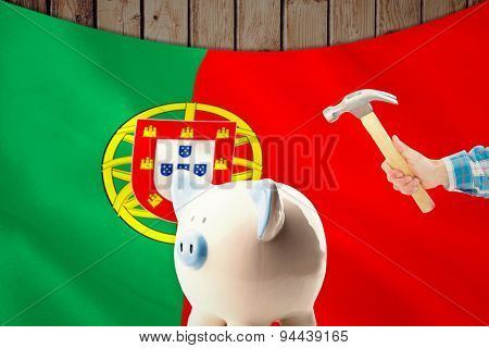 hand holding hammer against digitally generated portugese national flag