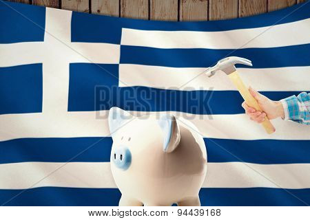 hand holding hammer against digitally generated greek national flag