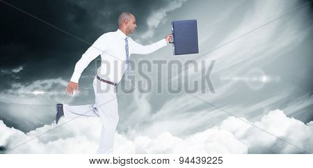 Businessman running with briefcase against blue sky