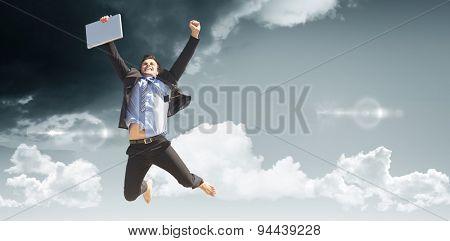 Cheering businessman against blue sky