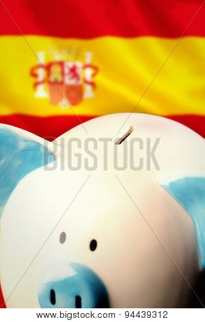 Piggy bank against digitally generated spanish national flag
