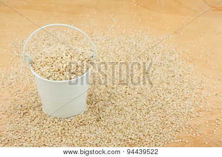White Bucket With Sesame Seeds  On The Wooden Floor