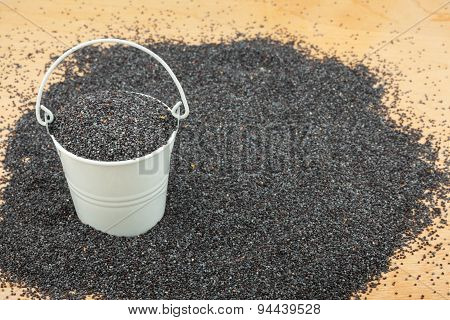White Bucket With Poppy Seeds  On The Wooden Floor