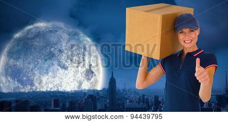 Happy delivery woman holding cardboard box showing thumbs up against large moon over city