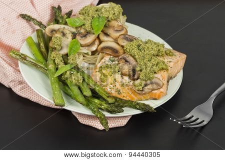 Delicious grilled salmon with creamy pesto sauce asparagus and linguine on the side