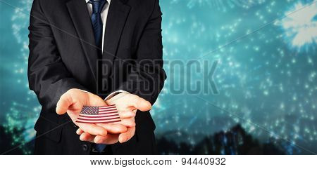 Mature businessman holding his hands out against colourful fireworks exploding on black background