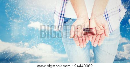 Hipster showing her hands against colourful fireworks exploding on black background