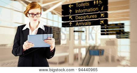 Redhead businesswoman using her tablet pc against airport