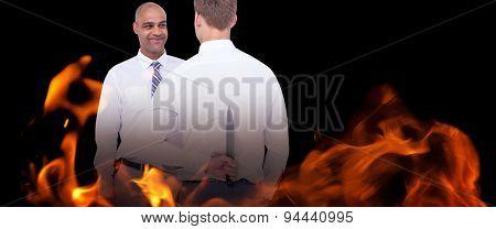 Businessman holding knife behind his back against black