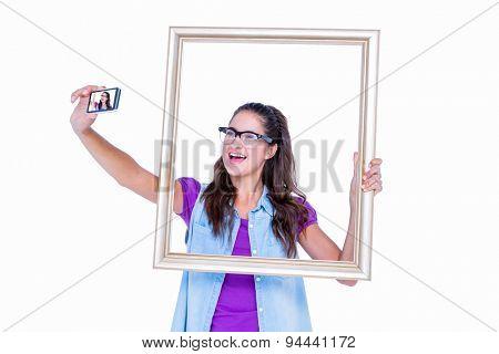 Pretty brunette taking a selfie on white background