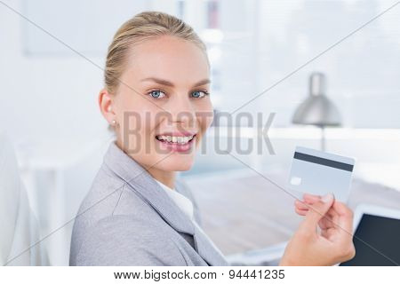 Smiling businesswoman looking at camera with credit card in her office