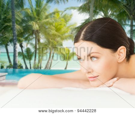 people, beauty, spa and body care concept - happy beautiful woman lying on massage desk at resort over sea and pool on tropical beach with palms background