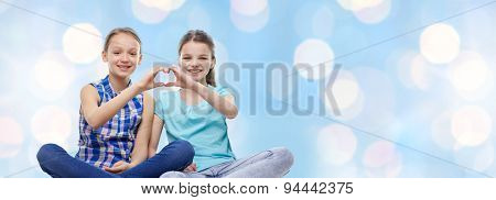 people, children, friends and friendship concept - happy little girls sitting and showing heart shape hand sign over blue holidays lights background