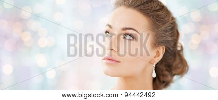 people, beauty, jewelry and accessories concept - beautiful woman with diamond earrings over blue holidays lights background