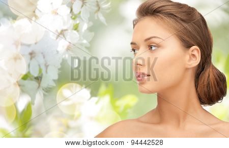 beauty, people and health concept - beautiful young woman face looking aside over green blooming garden background