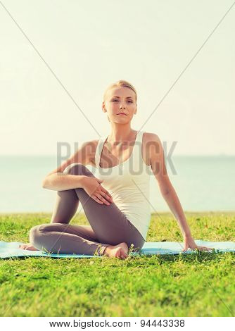 fitness, sport, friendship and lifestyle concept - smiling woman making yoga exercises sitting on mat outdoors