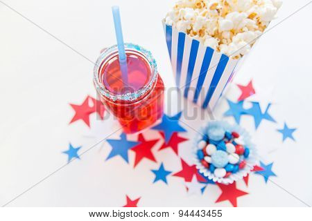 american independence day, celebration, patriotism and holidays concept - close up of juice glass or mason jar, popcorn and candies with stars confetti decoration at 4th july party
