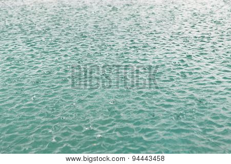 weather, rain, met cast, season and natural phenomenon concept - water surface with raindrops