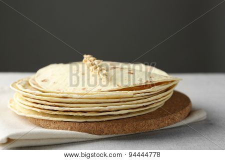 Stack of homemade whole wheat flour tortilla on napkin, on  dark background