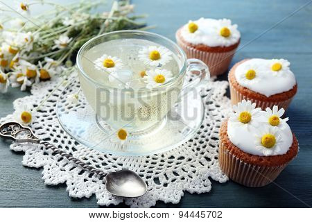 Cup of chamomile tea with chamomile flowers and tasty muffins on color wooden background