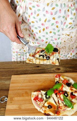 Housewife holding a baked pizza