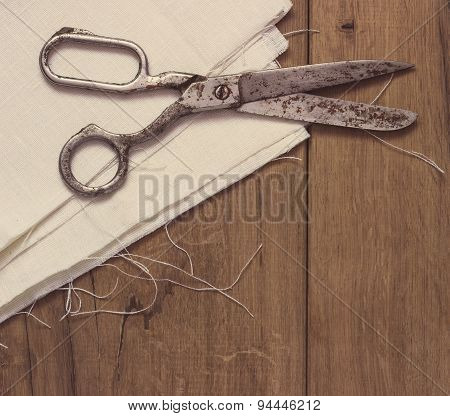 Old sewing scissors on the wooden background