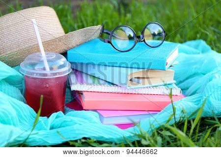 Books, glasses and drink on grass close-up