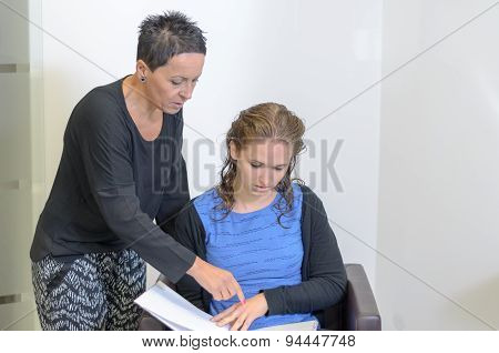 Hairdresser Woman Explaining To A Female Customer
