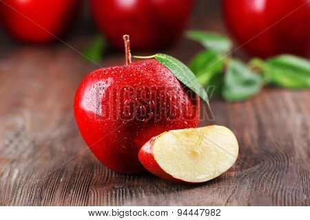 Red apples with droplets on wooden table, closeup