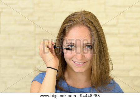Pretty Young Woman Applying Eyeliner