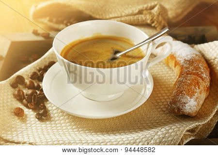 Cup of coffee with cookie on table, closeup