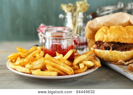 Tasty sandwiches and french fries on plate, on wooden background. Unhealthy food concept