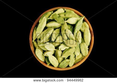 Cardamom in wooden bowl, on black background