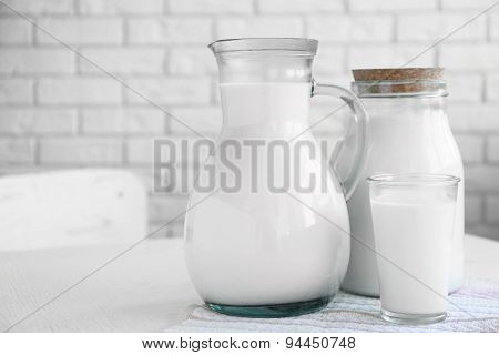 Pitcher, jar and glass of milk on wooden table, on bricks wall background