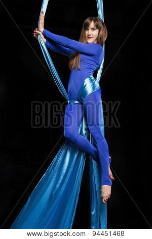 Young gymnast training on aerial silk