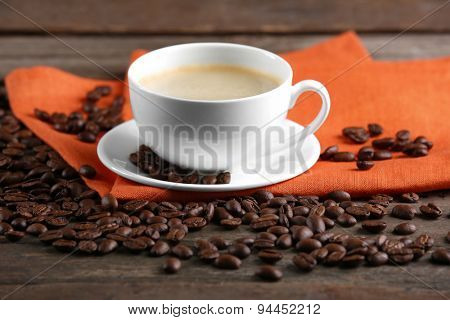 Cup of coffee and beans on table close up