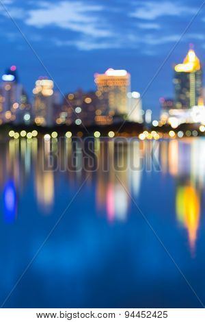 Water reflection of bokeh city lights during twilight